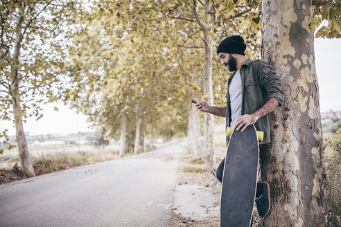 Spain, Tarragona, young man with longboard leaning against tree trunk looking at his smartphone - JRFF000191