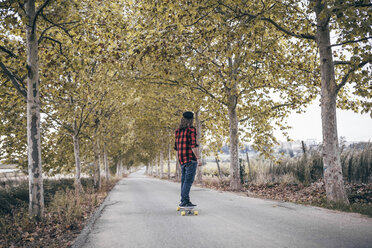 Spain, Tarragona, back view of man with longboard on autumnal country road - JRFF000194