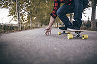 Man standing on longboard on a country road, partial view - JRFF000197