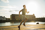 Young man running by the riverside - UUF005946
