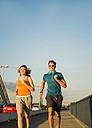 Young couple running on a bridge - UUF005961
