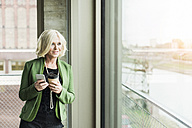 Portrait of blond businesswoman with coffee to go and smartphone looking through window - UUF005977