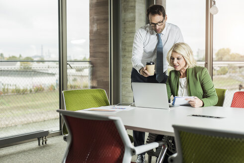 Two business people looking at laptop in an office - UUF005995