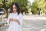 Portrait of young woman looking at her smartphone - RAEF000637