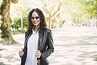Portrait of smiling woman wearing sunglasses and leather jacket in a park - RAEF000643