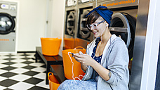 Smiling young woman hearing music with earphones in a launderette - MGOF001025