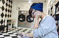 Young woman hearing music with earphones in a launderette - MGOF001028
