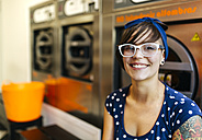 Portrait of smiling young womanwearing glasses  in a launderette - MGOF001040