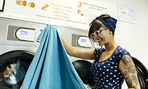 Portrait of tattooed young woman in a launderette - MGOF001043