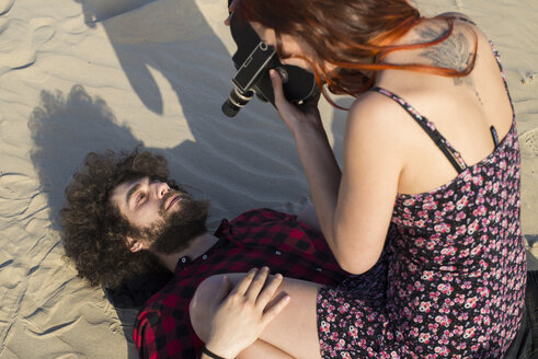 Young woman filming her boyfriend on the beach - KIJF000029
