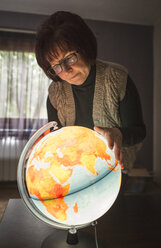 Senior woman looking at lighted globe - DEG000575