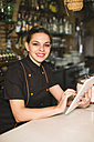 Portrait of smiling waitress in bar with digital tablet - JASF000243
