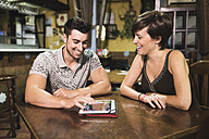 Happy couple sitting at a table in a bar using digital tablet - JASF000246