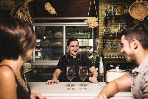 Laughing waitress and couple at bar with red wine glasses - JASF000249