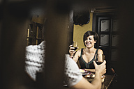 Smiling couple holding red wine glasses in a restaurant - JASF000258