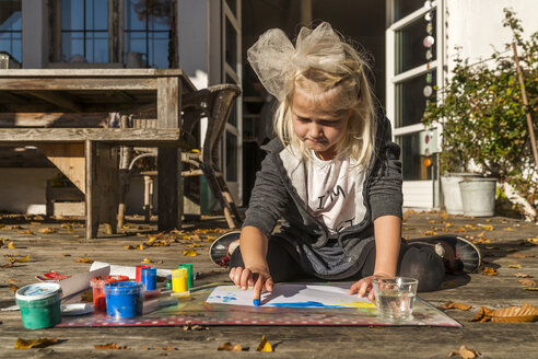 Blond little girl painting with finger colours on the terrace - TCF004921