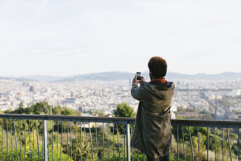 Spain, Barcelona, back view of young man taking a picture of view with his smartphone - EBSF001044