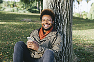 Portrait of smiling young man with smartphone leaning against tree trunk - EBSF001056