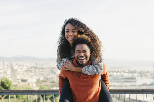 Spain, Barcelona, portrait of laughing young man giving his girlfriend a piggyback ride - EBSF001062
