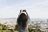 Spain, Barcelona, back view of young woman taking a picture of view with her smartphone - EBSF001077