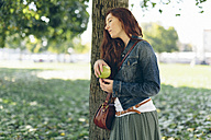 Relaxed woman holding an apple in park - GIOF000495