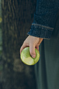 Hand holding a green apple outdoors - GIOF000498