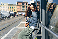 Italy, Padua, woman at the bus stop holding a cell phone - GIOF000507
