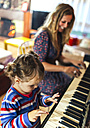 Woman and little girl playing piano together - MGOF001048