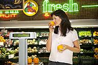 Customer smelling orange in a supermarket - RMAF000221