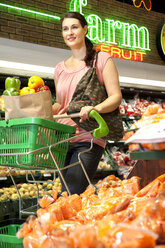 Portrait of smiling customer with shopping cart buying vegetables in a supermarket - RMAF000224