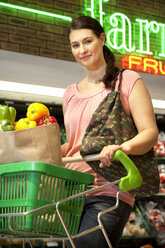 Portrait of smiling customer with shopping cart buying vegetables in a supermarket - RMAF000227