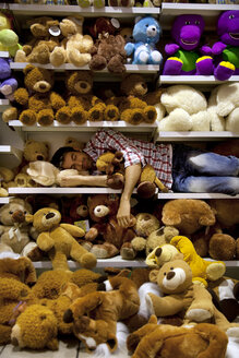 Man sleeping on a shelf between soft toys in a supermarket - RMAF000230