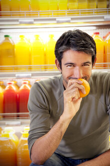 Portrait of smiling man sitting in front of fridge with rows of juice bottles in a supermarket smelling orange - RMAF000233