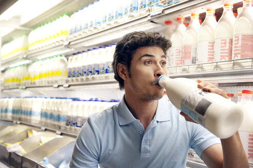 Man drinking milk in front of fridge in a supermarket - RMAF000245