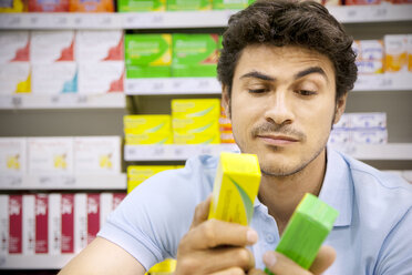 Portrait of a man in a supermarket comparing two products - RMAF000248