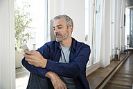 Mature man working from home using smart phone - FKF001538