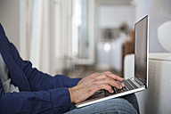 Mature man working from home using laptop - FKF001544