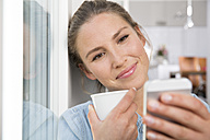 Young woman sitting at the window, drinking coffee an reading sms - FKF001550