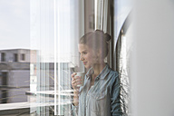 Young woman standing at the window, drinking coffee - FKF001553