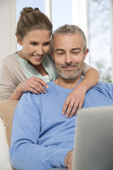 Couple sitting on couch using lapto - FKF001574