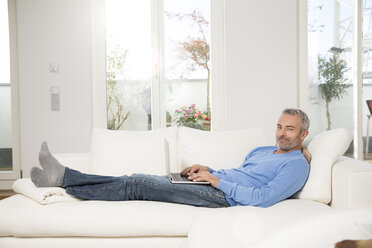 Mature man at home, sitting on couch, using laptop - FKF001577