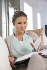 Young woman sitting on couch, reading book - FKF001580