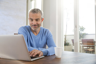 Mature man working from home using laptop - FKF001583