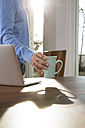 Mature man working from home putting cup on table next to laptop - FKF001586