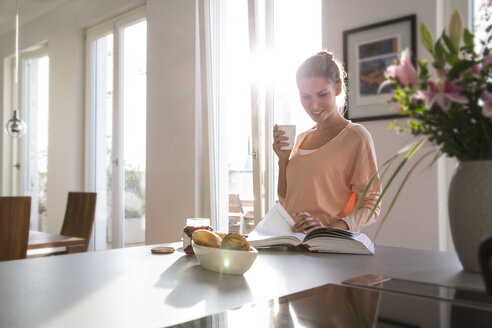 Young woman in kitchen having breakfast in kitchen, paging through book - FKF001595