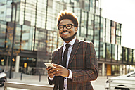 Smiling young businessman outdoors with cell phone - EBSF001090