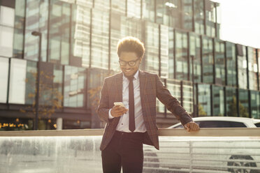 Smiling young businessman outdoors looking at cell phone - EBSF001093