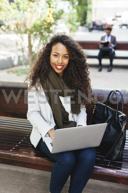 Smiling young woman using laptop on bench - EBSF001096 - Bonninstudio/Westend61