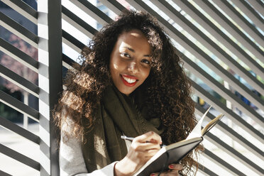 Portrait of smiling young woman with notebook outdoors - EBSF001105