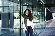 Portrait of smiling young woman leaning against glass front - EBSF001108